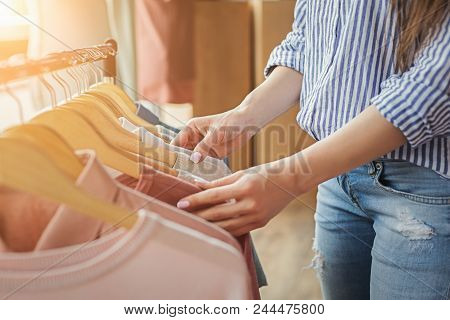 Unrecognizable Woman Choosing Clothes On Rack In Showroom. Sale, Fashion And Consumerism Concept, Cr