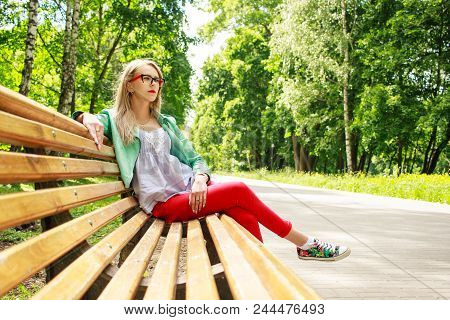 Cute Girl In Jeans And A Jacket Is Sitting On A Park Bench