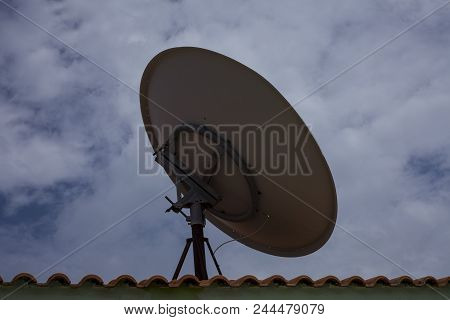 Parabolic Dish Antenna Held On The Roof Top Of A Building. It Is Used By Consumers To Receive Direct