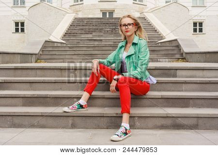 Portrait Of A Beautiful European Woman In Glasses Sitting On Steps.