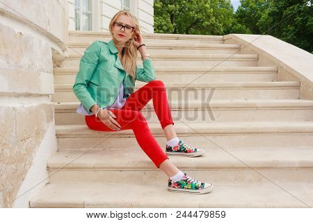Portrait Of A Beautiful European Woman In Glasses Sitting On Marble Staircase