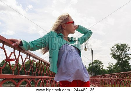 Young Blond Woman In Leather Jacket And Glasses Posing On Red Bridge Looking Into The Sky. The Wind