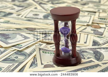 The Concept Of Time Is Money. Sand Clock, Hourglass, Sand Timer On A Pile Of Dollars And Coins. Clos