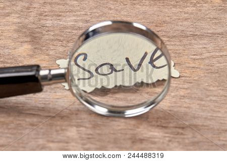 Magnifier And Save Concept. Close Up. Magnifying Glass Zooming Word.
