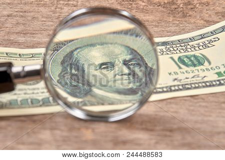Hundred Dollar Bill Under A Magnifying Glass. Close Up. Us Dollars Brighten Under Magnifying Glass S