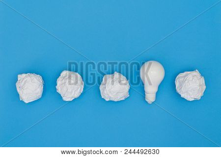 Creativity Inspiration, Ideas Concepts With Lightbulb And Paper Crumpled Ball On Blue Color Backgrou