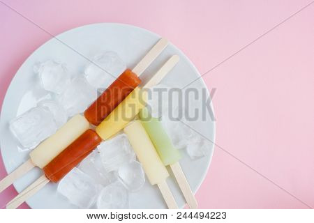 Flat-lay Of Vegan Vegetarian Colorful Ice Cream Popsicles, Ice Cream Sticks With Ice Cubes On White