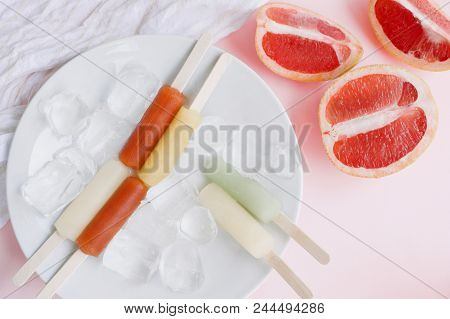Flat-lay Of Vegan Vegetarian Colorful Popsicles With Ice Cubes On White Plat And Fruits Over Pink Pa