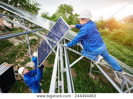 Installing of stand-alone solar photo voltaic panel system. Team of three technicians in hard-hats mounting the solar module on platform on green summer view background. Alternative energy concept. poster