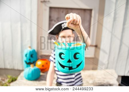 Boy In A Pirate Costume Holds A Bucket With Inedible Gifts.  Teal Pumpkin Project. Alternative Non-f