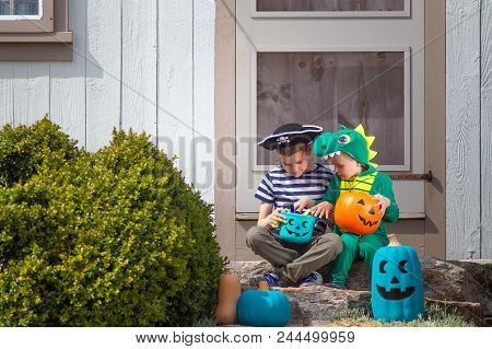 Halloween Kids Sitting On Porch Trick Or Treating.  Teal Pumpkin Project. Alternative Non-food Treat