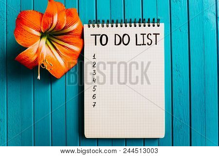 Inscription To Do List On A Blank Sheet Of A Notebook With Flower On A Turquoise Wooden Background,
