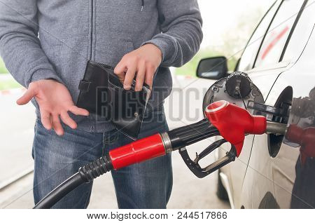 Lack Of Money For Gasoline And Fuel. Expensive Gasoline. Driver Man Holds One Dollar End Empty Walle