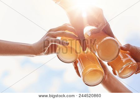Summer, Leisure, Celebration And Drinking Concept. Close Up Shot Of Four Hands Clink Bottles With Le