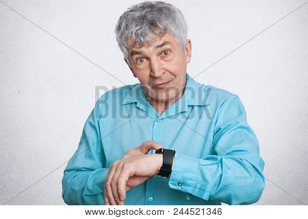 Handsome Male Pensioner With Wrinkles On Face, Looks At Smartwatch With Health Application, Checks T