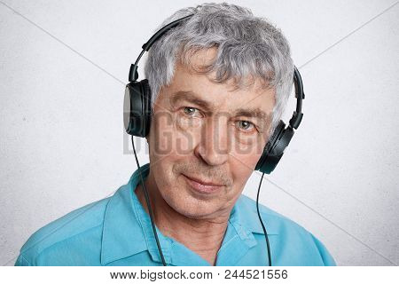 Close Up Portrait Of Serious Grey Haired Male Wears Headphones, Looks Seriously At Camera, Enjoys Go