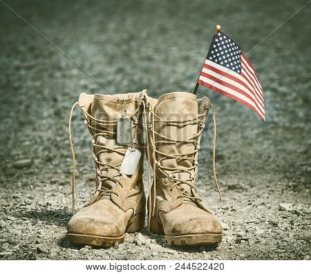 Old Military Combat Boots With The American Flag And Dog Tags. Rocky Gravel Background. Memorial Day