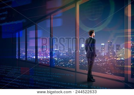 Side View Of Young Businessman Looking Out Of Window In Interior With Digital Interface And Night Ci