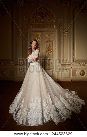 Fashion Portrait Of Beautiful Woman In Long Elegant White Dress. Girl With Elegant Hairstyle. Bridal