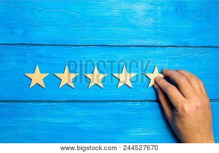 A Female Hand Puts The Fifth Wooden Star On A Blue Background. The Critic Sets The Quality Rating. F