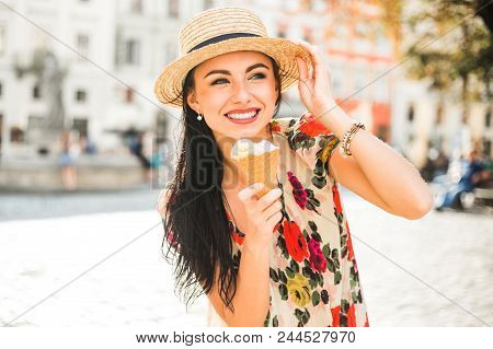 Young Beautiful Girl In Summer Dress, Straw Hat. Travels Around The European City In The Summer. A C