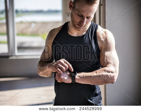 Young Attractive Man In Gym Checking Sports Watch To Track His Workout, Heart Pulse Or Fitness