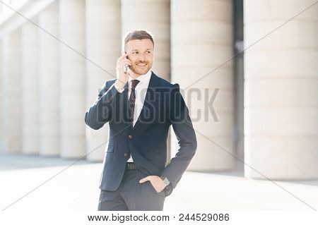 Cheerful Male Entrepreneur Has Phone Conversation, Looks Confidently And Happily Aside, Dressed In F