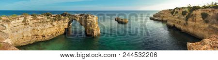 Panoramic View Of The Natural Arch Arco  Da Albandeira In The Algarve, Portugal. The Arch And Surrou