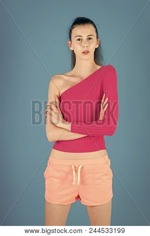 Fashion Model Pose In Studio On Blue Background. Woman With Brunette Hair And No Makeup. Girl In Ora