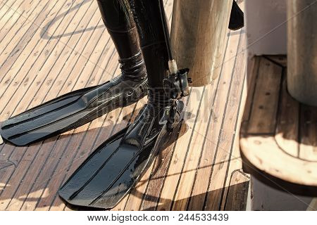 Diving. Legs In Black Rubber Wetsuit And Flippers On Wooden Deck Equipment For Scuba Diving On Summe