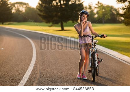 Pretty Woman Biker Posing With Bicycle Outdoors. Girl With Bike On Coutry Road. Summer Relax Outdoor