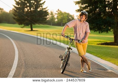 Smiling Man Resting With Bicycle On Country Road. Happy Young Man In Casual Wear Having Rest With Bi