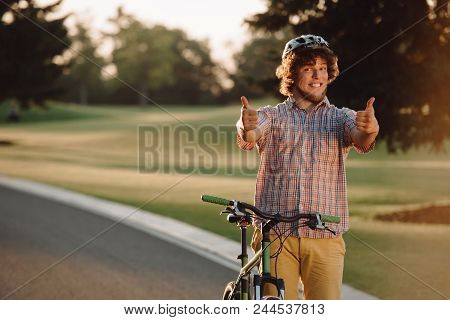 Happy Cyclist Giving Two Thumbs Up Outdoors. Portrait Of Cheerful Guy With Bike Gesturing Thumbs Up.
