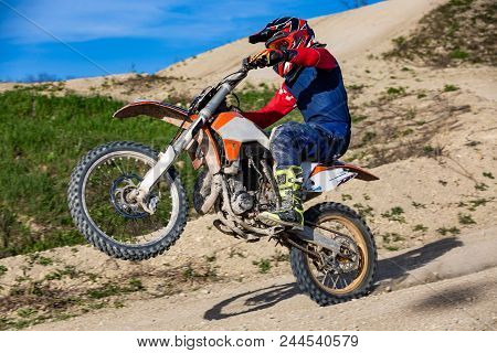 Professional Motocross Motorcycle Rider Drives Over The Mountain Road Track.