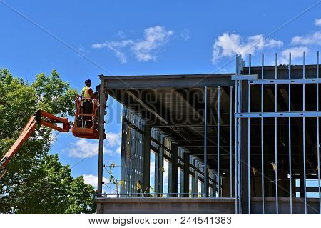 Two Unidentified Construction Workers In A Hydraulic  Hoist Basket Work On The Steel Framing Of A Ne