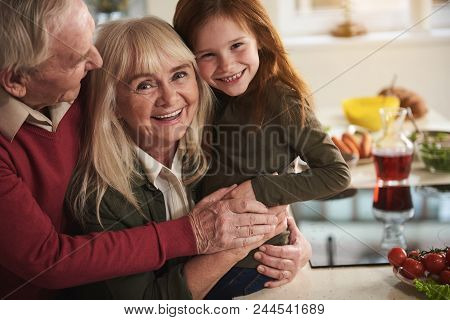 Portrait Of Smiling Grandparents Hugging Their Grandchild. They Are Holding Each Other With Joy With