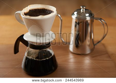Ceramic Hand Drip Coffee Brewer (dripper) And Drip Ground Coffee On A Glass Server With Stainless Dr