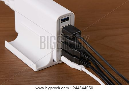 Multiport Charging Station And Charging Cables On A Wooden Background