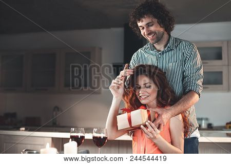 Portrait Of Happy Married Couple Celebrating Anniversary In Kitchen. Husband Is Holding A Gift Box I