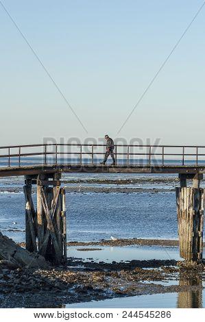 Plymouth, Massachusetts, Usa - February 17, 2007: Man Walking The Footbridge Over The Channel Throug