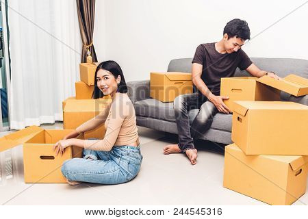 Happy Young Couple Unpacking Box And Moving Into Their New Home.house Moving And Real Estate Concept