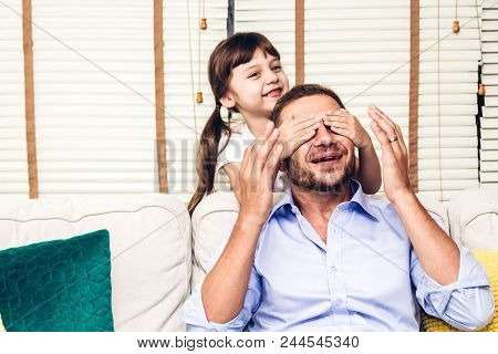 Father With Little Daughter Having Fun And Playing Close Eye Daddy On The Sofa At Home.little Girl