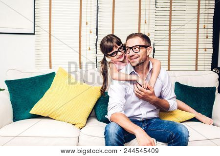 Father With Little Daughter Having Fun And Playing Together On The Sofa At Home.little Girl Hug Dadd