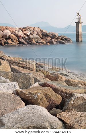 Lighthouse On A Rocky Breakwall: A Small Lighthouse Warns Of A Rough Shoreline.