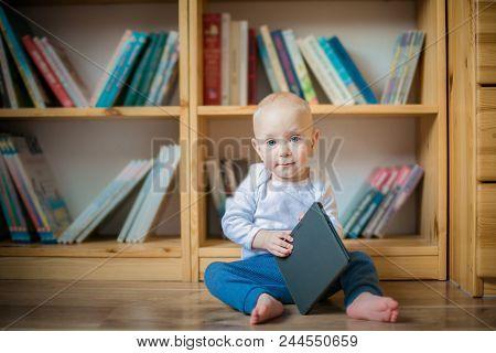 Toddler Girl Honding Ebook In Front Of Book Shelves. Education Concept