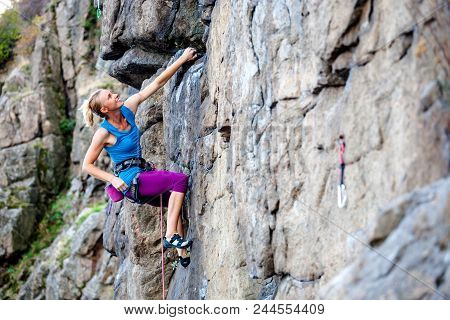 A Woman Climbs The Rock. Training On Natural Terrain. Extreme Sport. The Climber Trains On A Natural