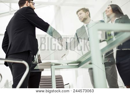 Bottom View : A Handshake Of Business Partners On The Background Of The Workplace.the Photo Has A Em