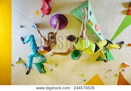 Rock Climbers In Climbing Gym. Young Couple Climbing Bouldering Problems (routes), Man Encouraging G