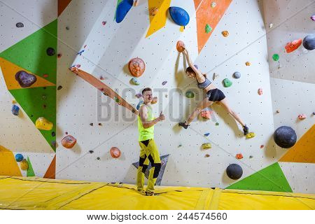 Rock Climbers In Climbing Gym. Young Woman Climbing Bouldering Problem (route), Male Instructor Show
