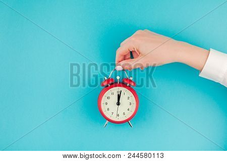 Creative Flat Lay Concept Top View Of Woman Hand In White Shirt Holding The Red Vintage Alarm Clock